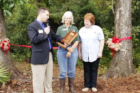 Philip Alia, Jacksonville Zoo Deputy Director of Marketing and Community Relations, presents an award in celebration of a successful partnership to Greenwood School science teacher Diane Krug and Principal Beverly Connell.  Over 80 people turned out to witness the grand opening of the Citizen Science Nature Trail.