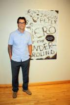 """Jason Peter poses by a poster for his book, """"Hero of the Underground."""" (Photo by FSCJ Author Series)"""