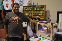 Eric Macedonia in Raptor Jesus T-Shirt, poses next to a 3D printer at Ancient City Con. (Photo by: Alvin Ogando)